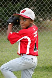 Young kid pitching in baseball wearing a red top, white long bottoms and a white hat: Baseball vs Softball [MindfuseBaseball.com]
