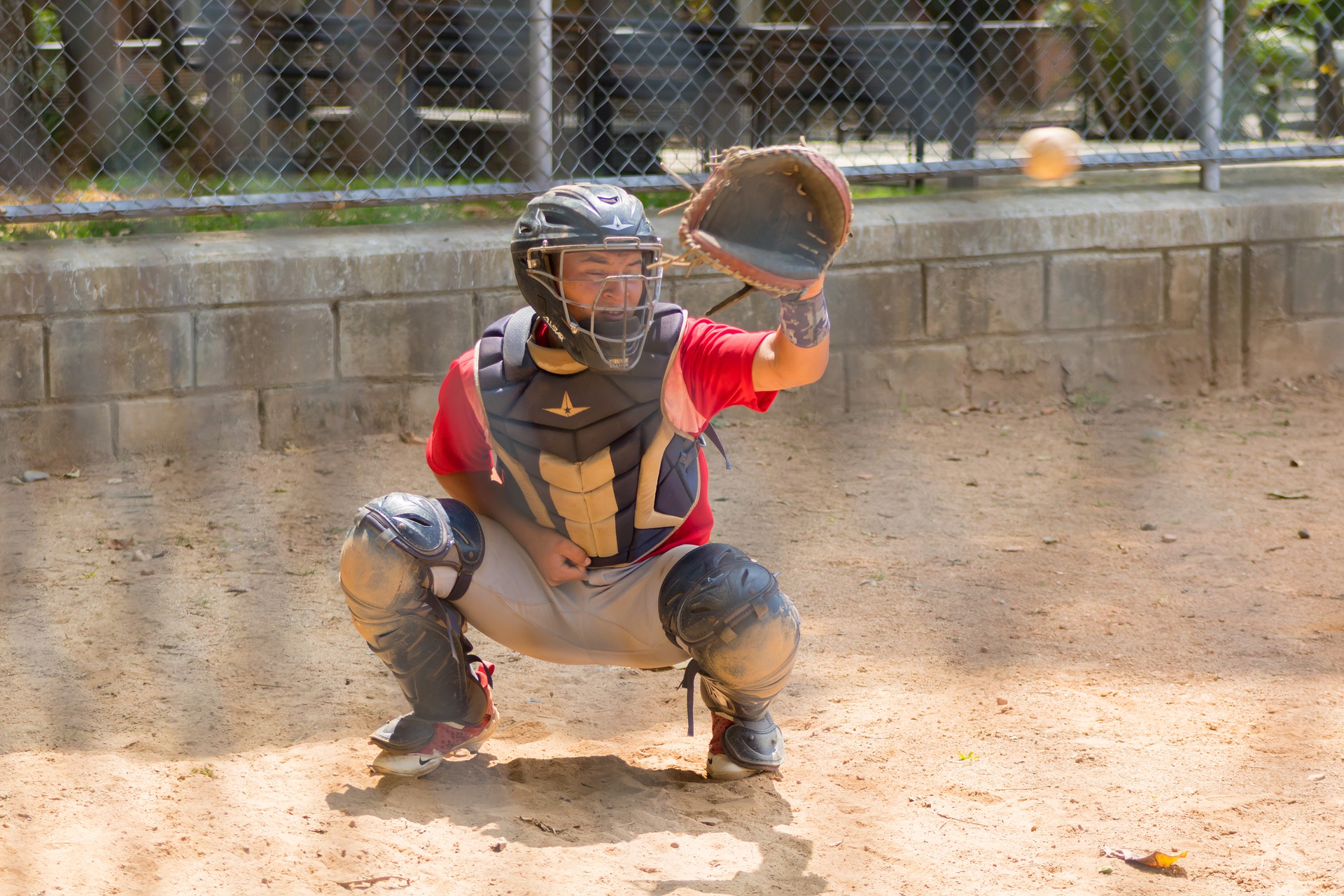A catcher hunched down in a game of baseball with their left arm outstretched ready to catch the ball: Types of Baseball Gloves [MindfuseBaseball.com]