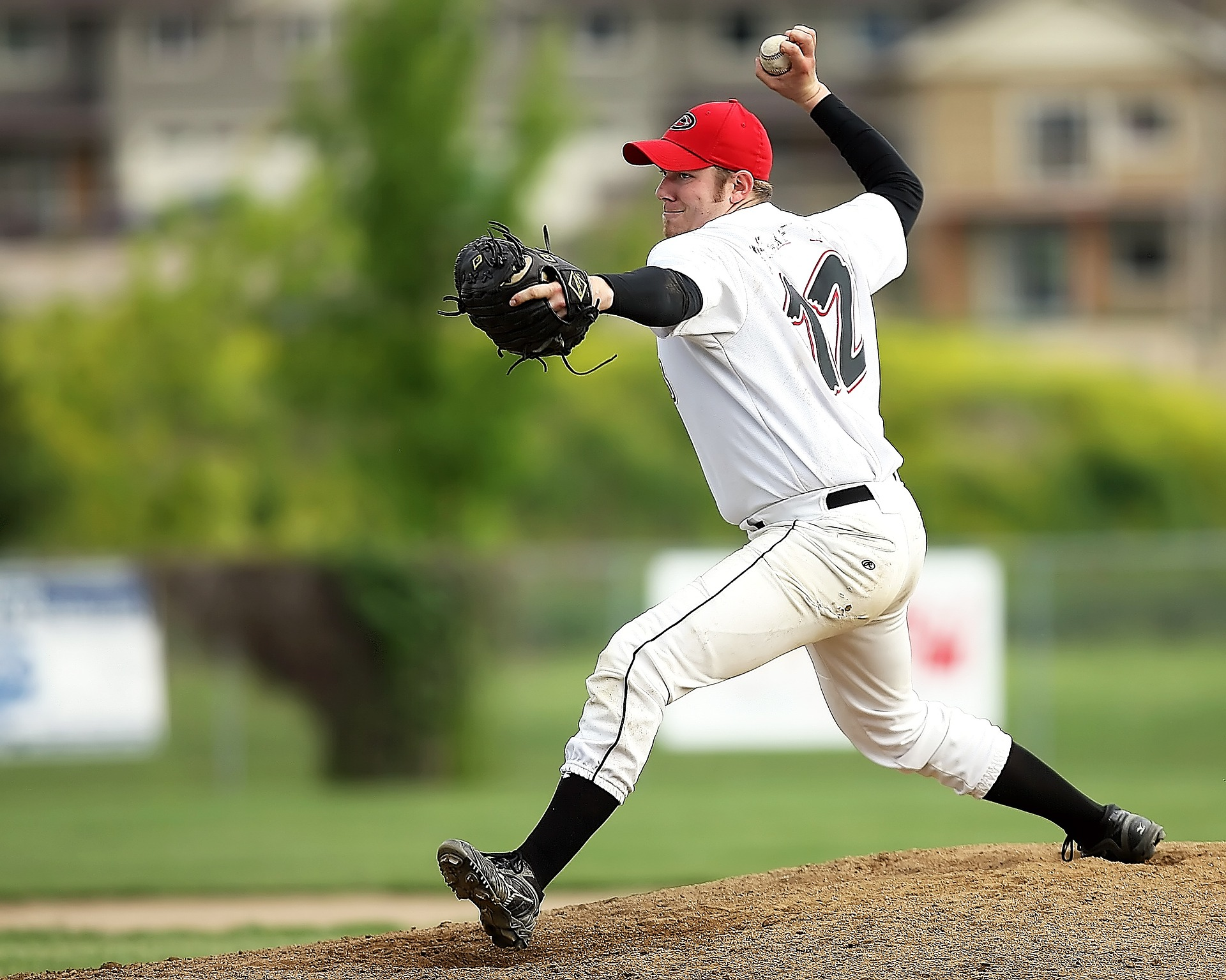 Baseball pitcher in white clothes and red hat just about to pitch a ball to the batter: Types of Baseball Gloves [Mindfusebaseball.com]