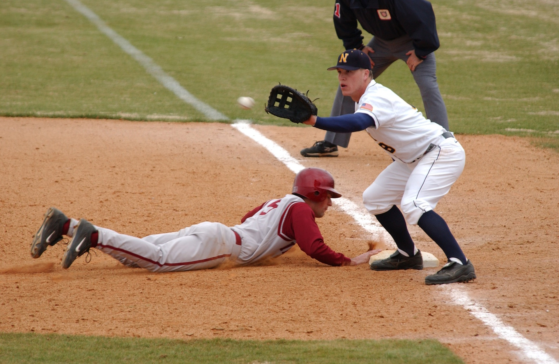 Runner sliding in head first to first base where the first basemen catcher is just about to catch the ball: Types of Baseball Gloves [MindfuseBaseball.com]