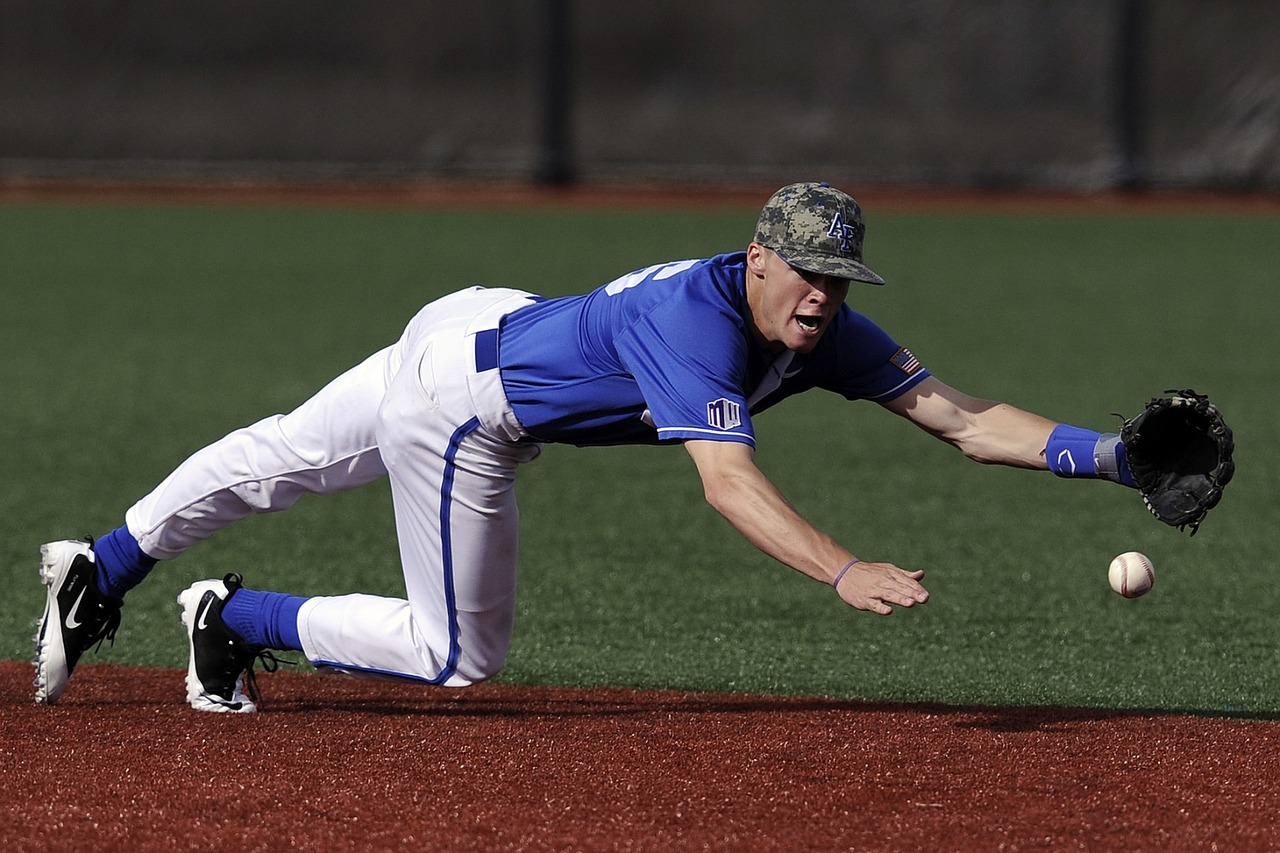 Baseball infielder diving to catch the ball with his left hand. He is wearing a blu top and white bottoms with a green hat on: Types of Baseball Gloves [MindfuseBaseball.com]