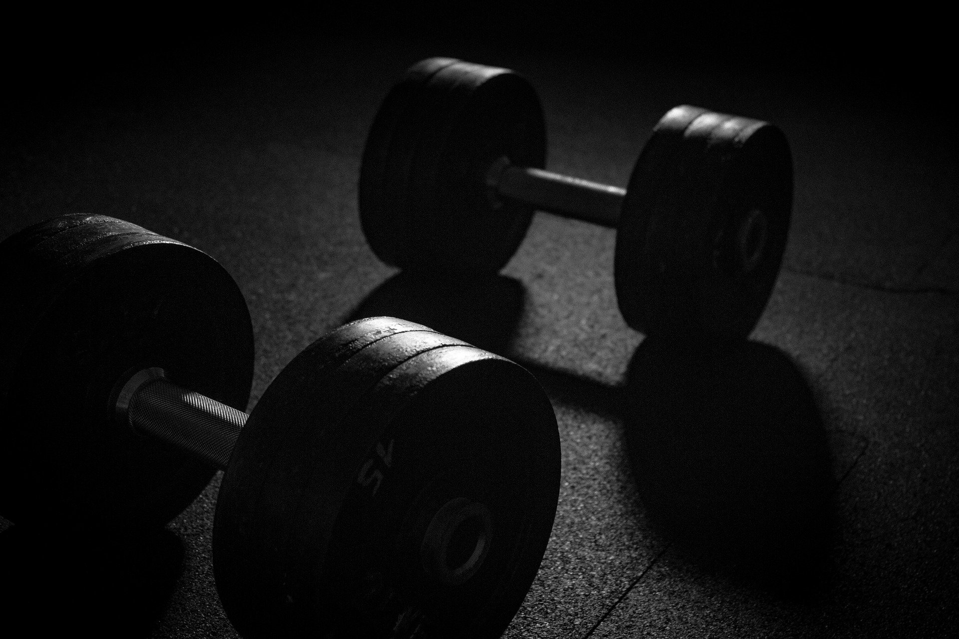 Two dumbbells on a gym floor. The picture has a dark tone to it: How To Throw a Baseball - FAST! [MindfuseBaseball.com]