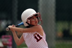 Young girl getting read to to bat in a game of softball. She's wearing a helmet and white top with the number 11 on it: Baseball vs Softball {MindfuseBaseball.com]